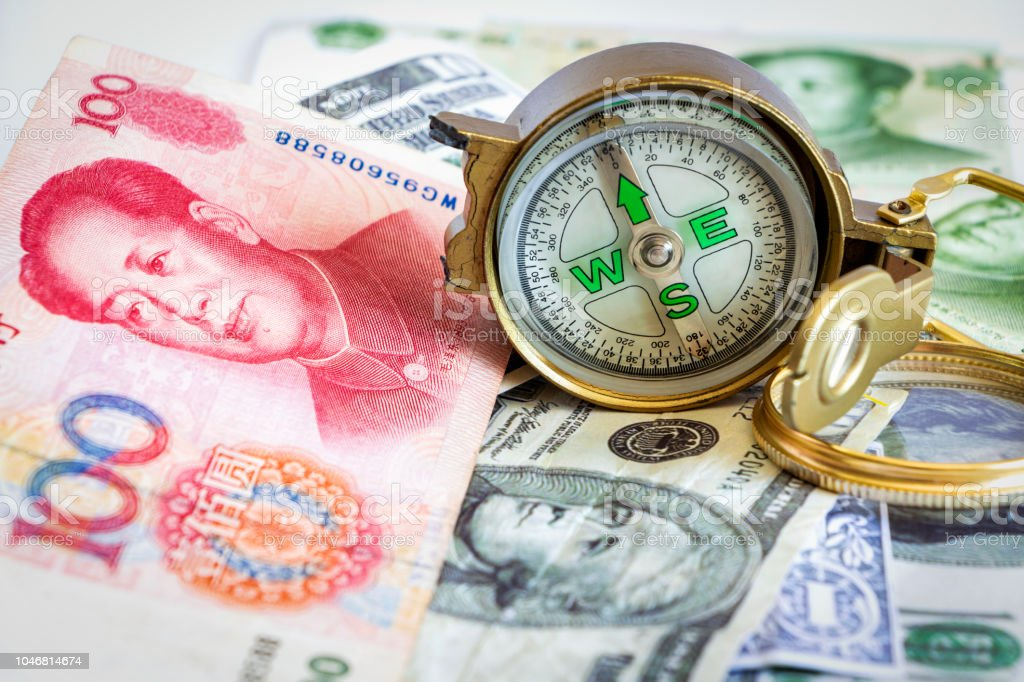 Defective compass placed on the dollar and yuan banknotes. The concept of direction of financial or investment at present and in the future. stock photo