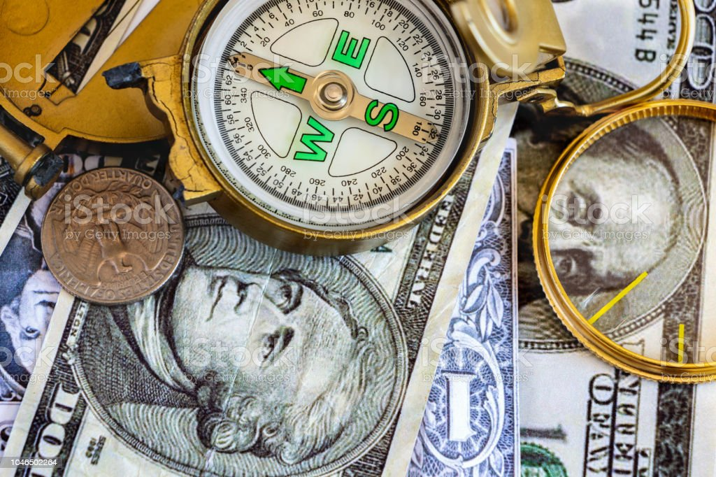 Defective compass placed on the United States dollar banknotes. The concept of direction of financial or investment at present and in the future. stock photo
