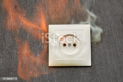 istock Defective wiring, fire plastic wall outlet. 1015605172
