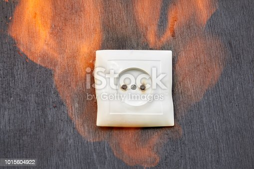 istock Defective wiring, fire plastic wall power socket. 1015604922