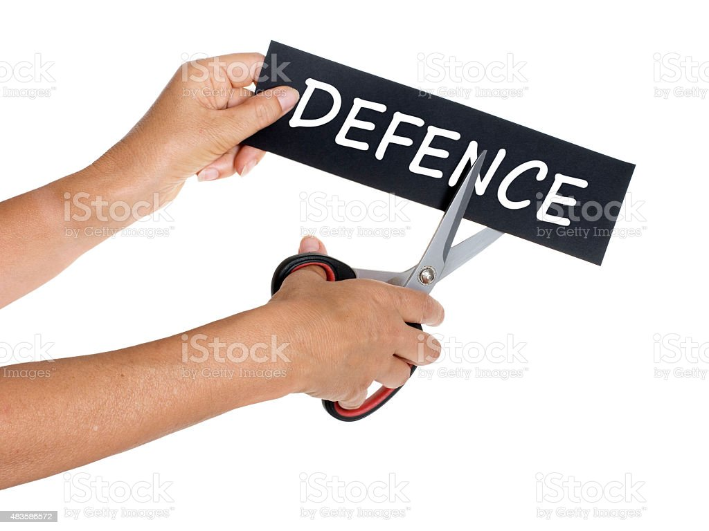 Defence cuts, concept. Hand with scissors isolated on white stock photo