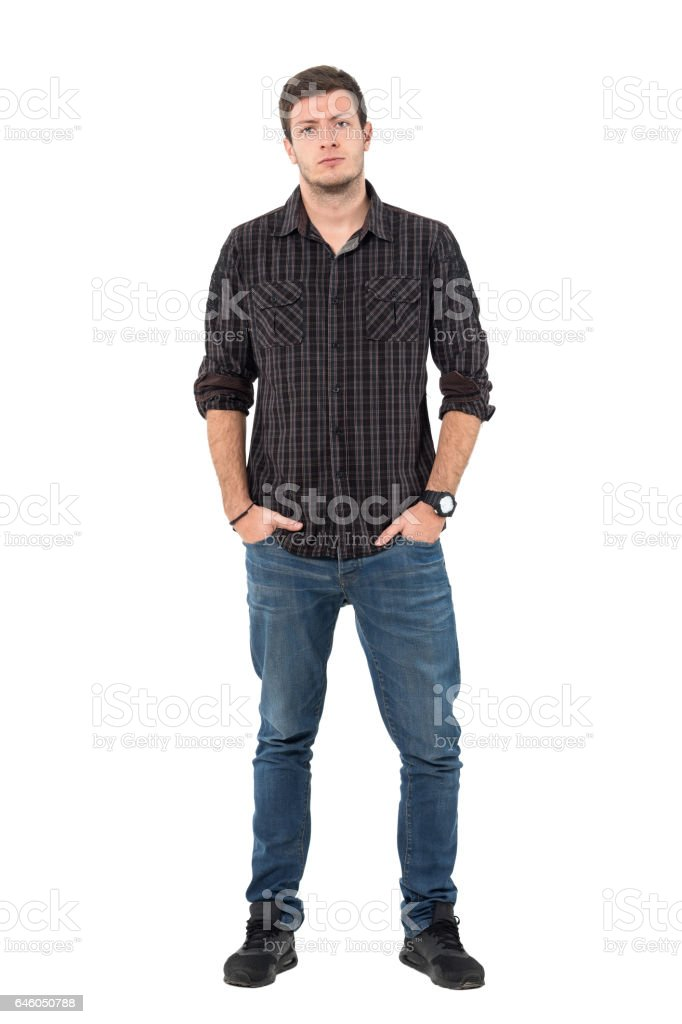 Defensive young man tilting head with hands in pockets stock photo