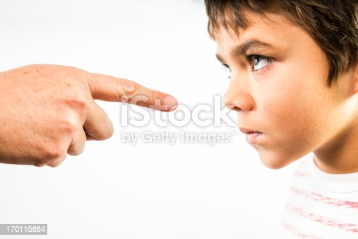 A photograph of a little boy being disciplined.  An angry child stares back in anger and defiance as he is being disciplined.  The finger of an adult is pointing directly at him.