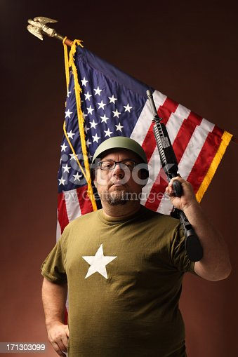 istock defiant GI soldier raises rifle in front of USA flag 171303099
