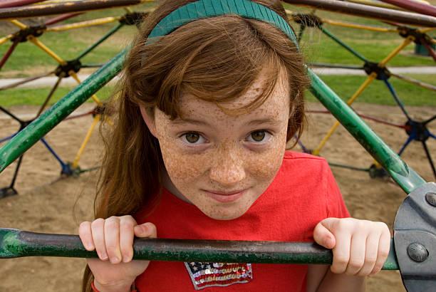 kampflustiger rotes haar mädchen auf schule-spielplatz - pailletten shirt stock-fotos und bilder