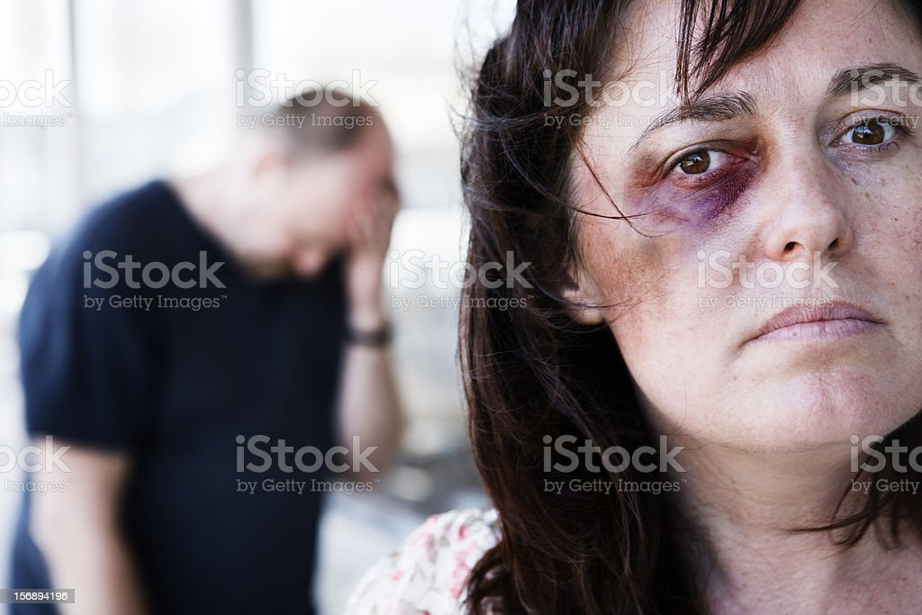 Defiant  victim of domestic abuse with depressed abuser stock photo