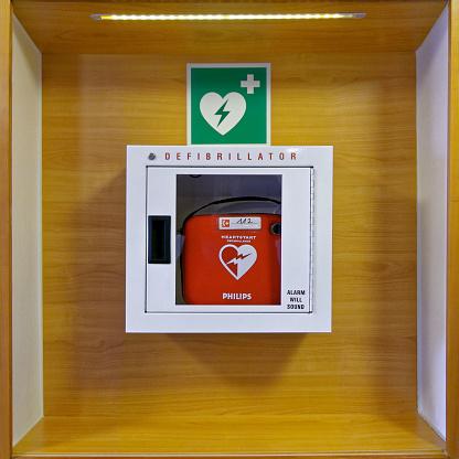 Zirndorf, Germany - January 31, 2018: Red heartstart external Defibrillator hangs on a wooden wall in a white box in a restaurant in Germany, Zirndorf.