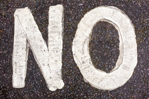 Definite No - word painted on road surface The word 'No' painted in capital letters on a dirty road surface. single word no stock pictures, royalty-free photos & images