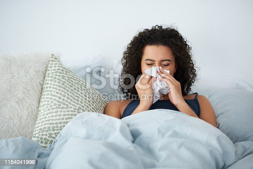 Shot of an attractive young woman feeling sick and blowing her nose while in bed in the morning