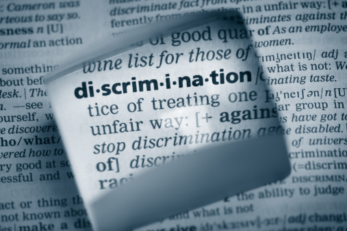 """The Dictionary definition of the word """"discrimination"""" photo taken through magnifying glass from a page of a dictionary with selective focus."""