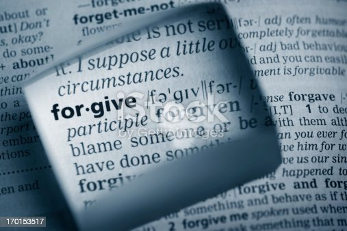 """The Dictionary definition of the word """"forgive"""" photo taken through magnifying glass from a page of a dictionary with selective focus."""