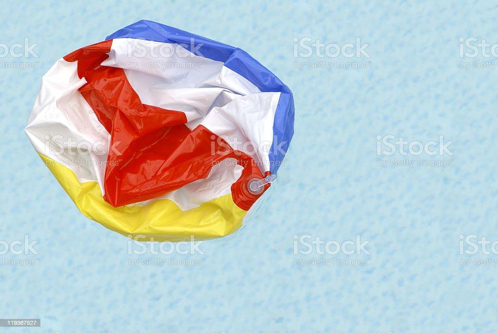 Deflated Beach Ball in Pool stock photo