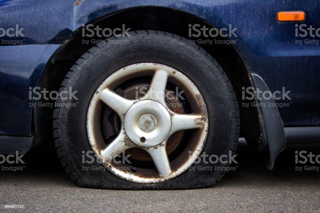 Deflated car tire stock photo