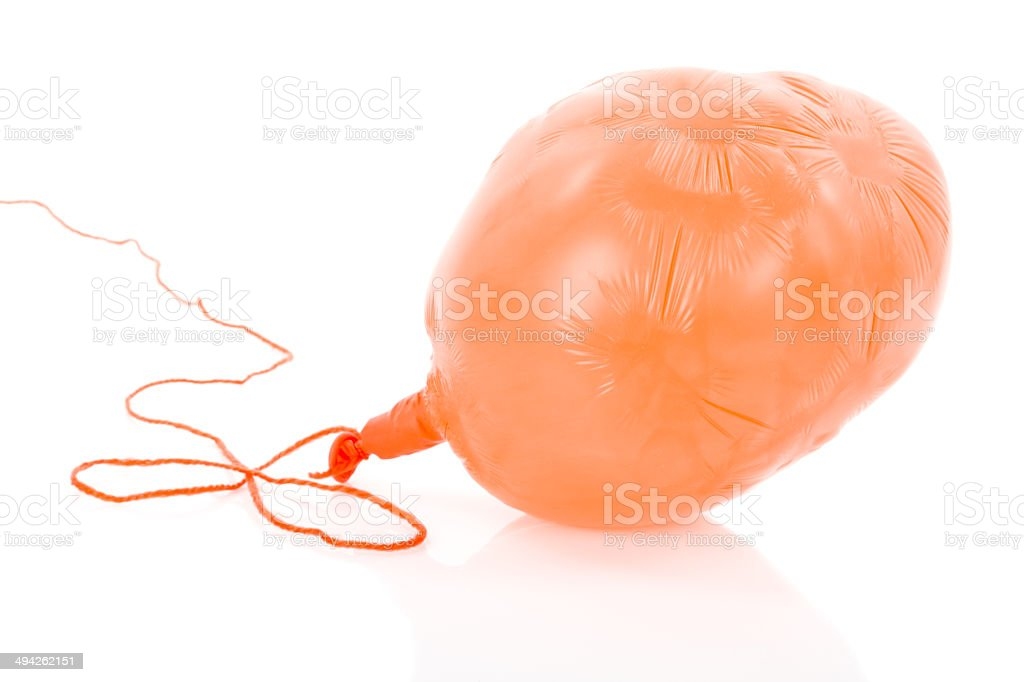 Deflated orange balloon isolated over white stock photo