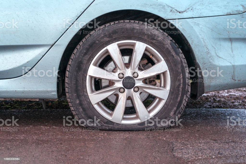 Deflated tyre damage to blue car wheel stock photo