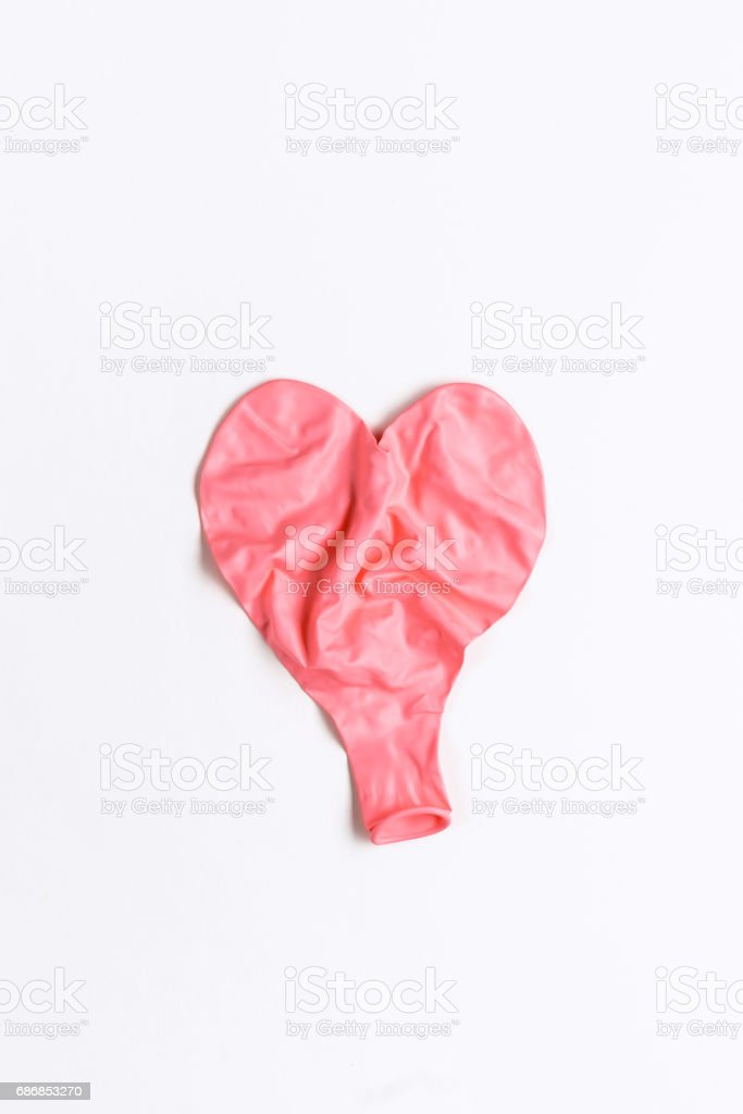 Deflated wrinkled pink heart shaped balloon laying flat on white background bildbanksfoto