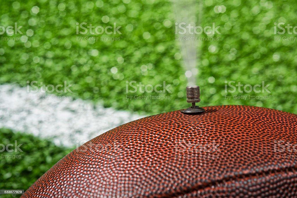 Deflate-Gate. NFL football deflated on the field stock photo