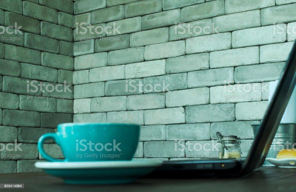 Desenfoque De La Taza De Cafe Azul Borrosa Y Ordenador Portatil