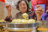 Defocus Senior Asian women eating Small  Steam Buns in Chinese Restaurant.beijing Capital City of china