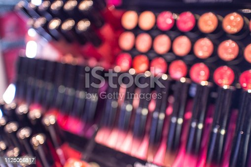 De-focused abstract image of colourful make up eyeshadows and lipsticks for sale on a counter in a store