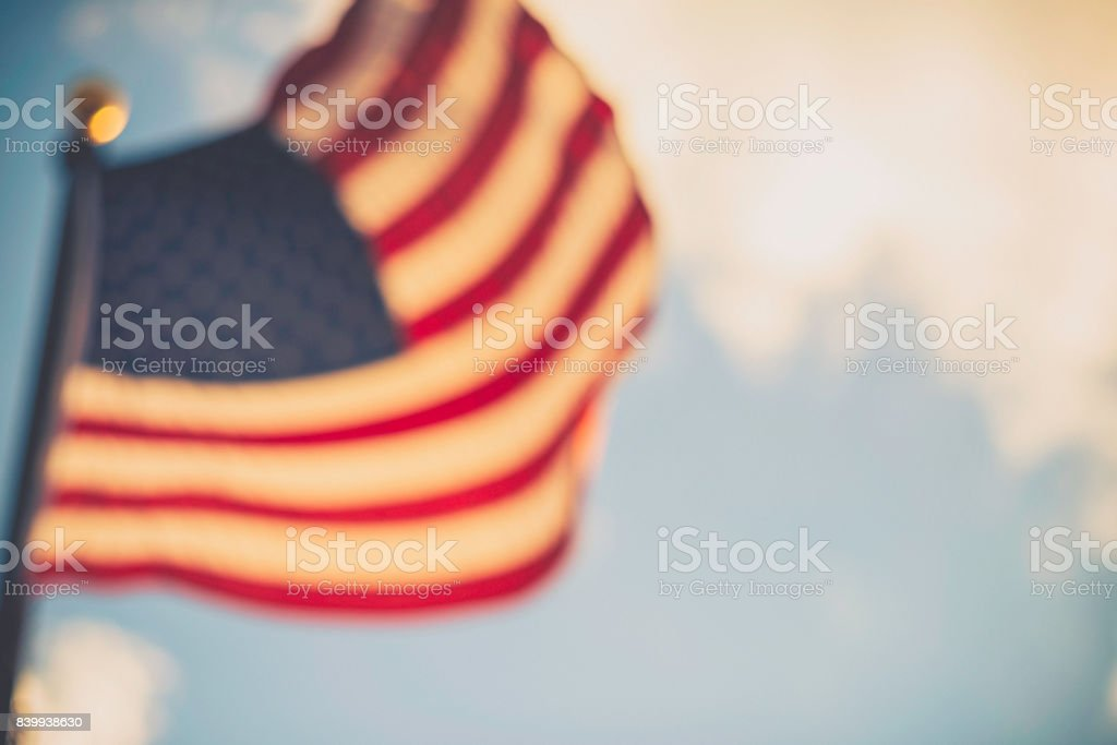 Defocused American flag against blue summer sky stock photo