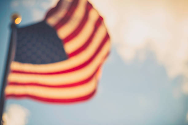 defocused american flag against blue summer sky - flag background stock photos and pictures