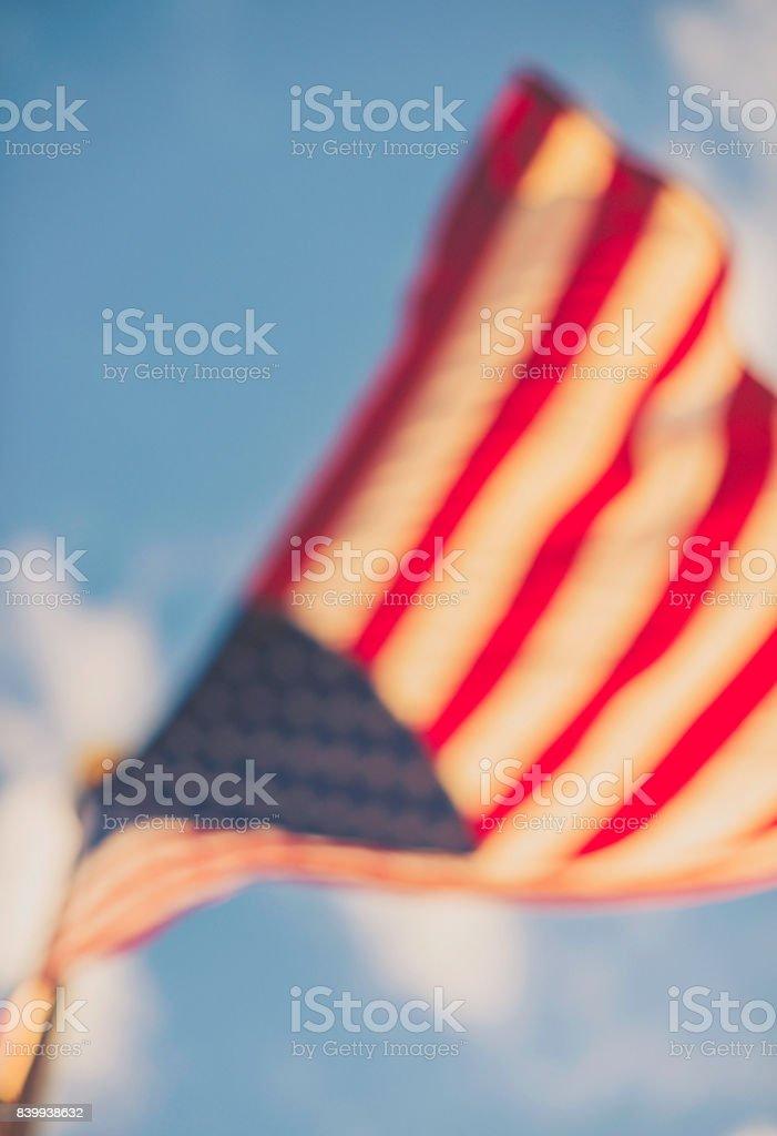 Defocused American flag against blue summer sky stock photo