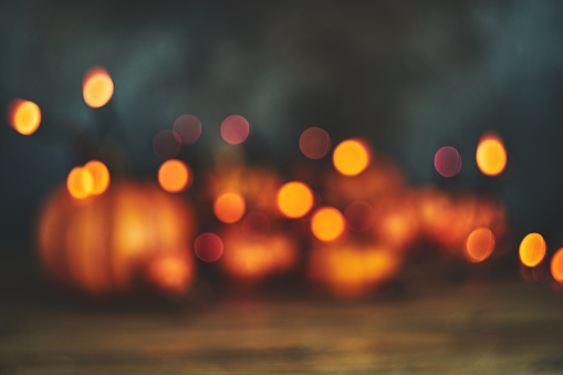 Defocused background with pumpkins and string lights for Halloween or Thanksgiving