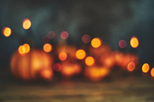 Defocused background with pumpkins and string lights for Halloween or Thanksgiving Defocused background with pumpkins and string lights for Halloween or Thanksgiving fall background stock pictures, royalty-free photos & images