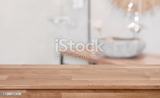 istock Defocused bathroom interior background with wooden table top in front 1138612408