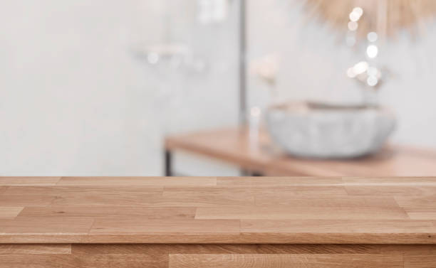 Defocused bathroom interior background with wooden table top in front stock photo