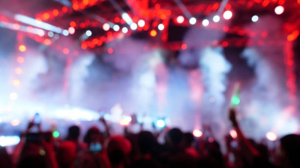 Defocused blur entertainment festival concert with crowd people raised hands and attending a concert. Blacklight by stage lights. Summer music festival concept. stock photo