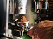 Defocused blur of Barista holding Coffee Machine Portafilter Filled with Ground Coffee Beans for making perfect shot of coffee. grinding coffee beans using  machine. Barista tools