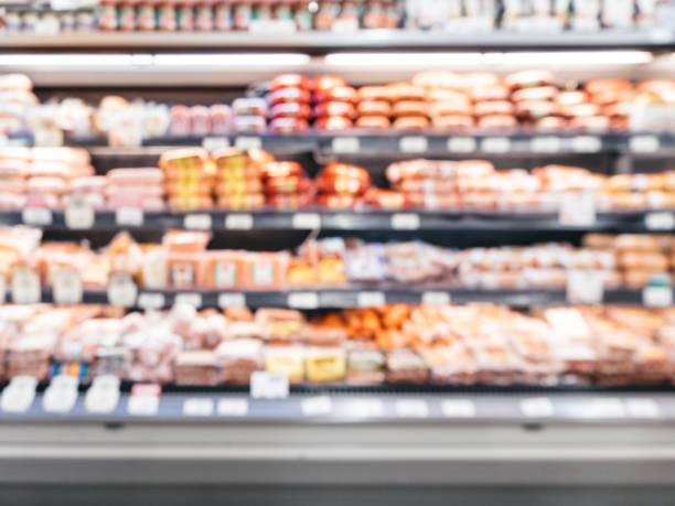 defocused blur of supermarket shelves with sausages in refrigerator - prodotti supermercato foto e immagini stock