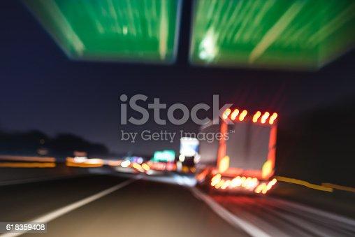 istock Defocused blurred motion of semitruck speeding on highway road speedway 618359408