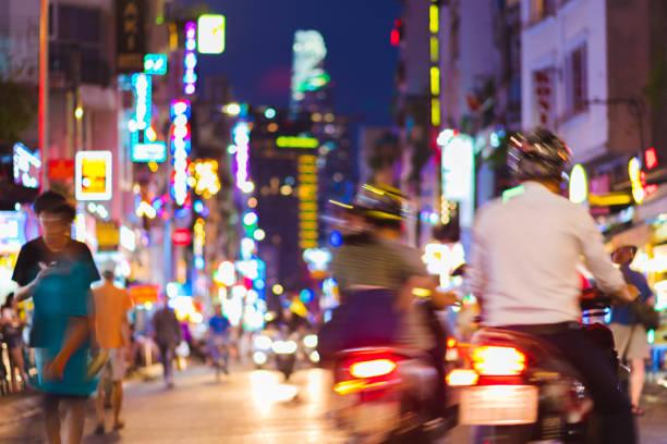 rue de nuit occupée défocalisée avec des néons - ho chi minh-ville (saigon), vietnam - moped photos et images de collection