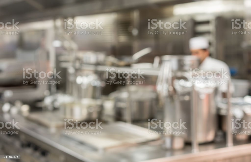 Defocused chef preparing food in commercial kitchen stock photo