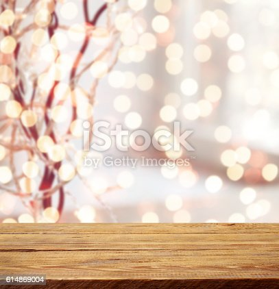 istock Defocused Christmas light and wooden background 614869004