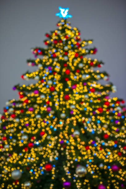 Defocused christmas tree silhouette with blurred lights stock photo