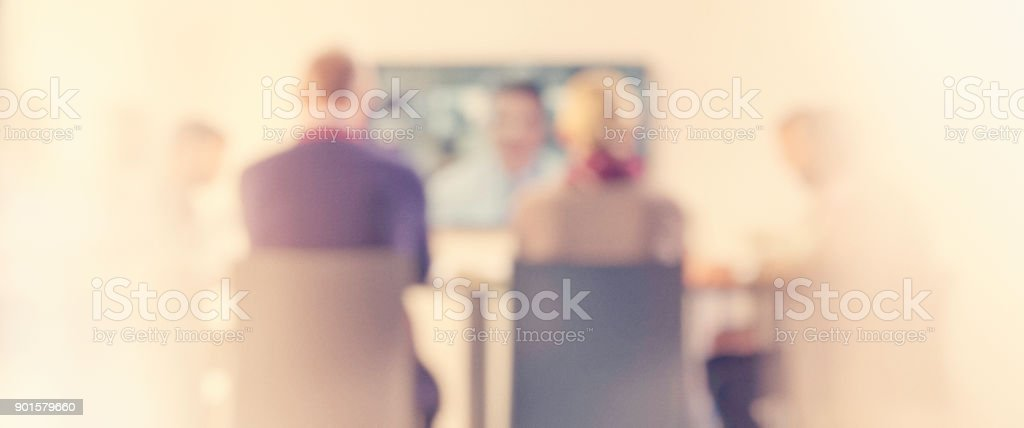 Defocused people at company video conference.