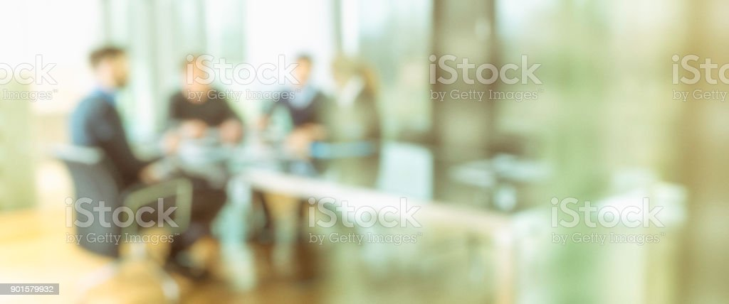 Defocused people at company meeting in conference room.