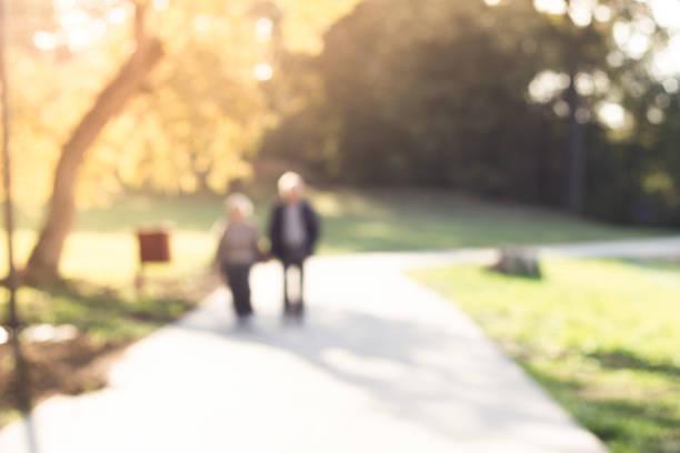 Defocused couple walking in public park stock photo