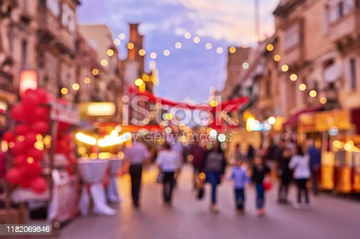 Defocused crowd of people during Christmas fair an old town street with colorful Christmas lights. Traditional Christmas market and shopping time concept