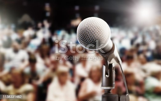 A concert, meeting,  or theatre audience awaits the performer or speaker. An empty mic is in the foreground.