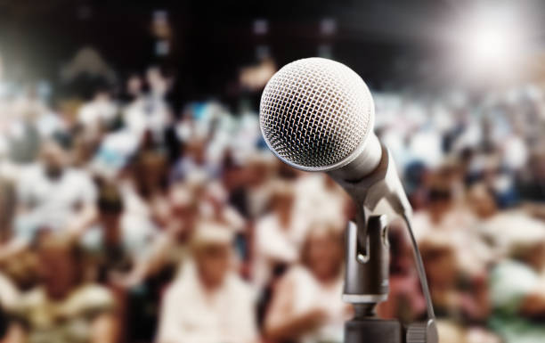 Defocused crowded audience with vocal microphone in foreground stock photo