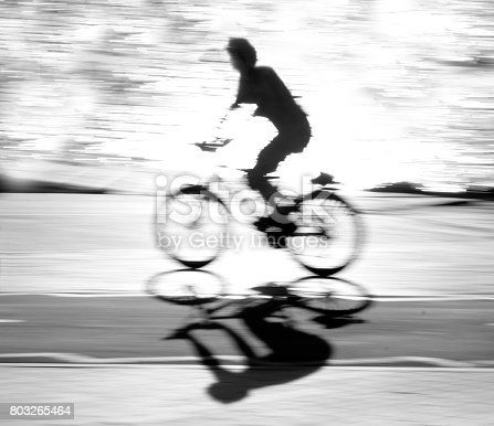 812812808 istock photo Defocused cyclist silhouette and shadow on a bike path 803265464