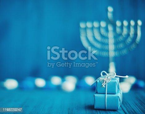 Defocused Hanukkah background with menorah, gifts and dreidel in blue setting
