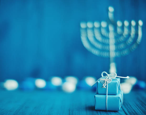 Defocused Hanukkah Background with Menorah, Gifts and Dreidel Defocused Hanukkah background with menorah, gifts and dreidel in blue setting hanukkah stock pictures, royalty-free photos & images
