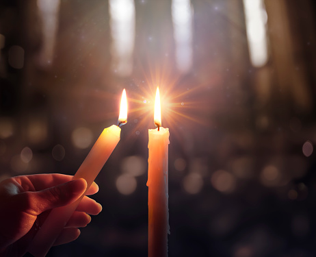 Sharing Concept - Hands Holding Candle With Shining Flame And Blurry Lights