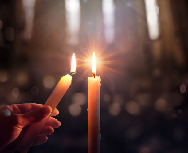 Defocused Hope Concept - Hand Igniting A Candle With Shining Flame And Blurry Lights stock photo